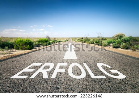 An image of a road to the horizon with text success in german language - stock photo