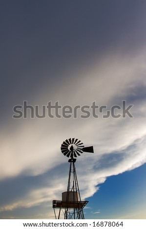 An image of a rustic windmill against a blue sky