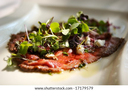 An image of a thinly sliced rare beef starter - stock photo
