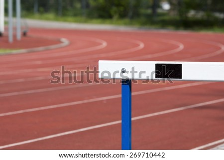 An image of a training hurdles in sunlight on a red surface.