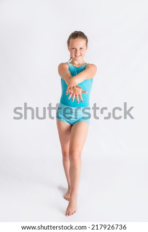 An image of a tween girl standing in blue leotard doing a gymnastics pose. - stock photo