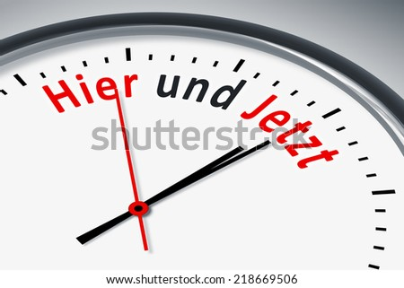 An image of a typical clock with text here and now in german language