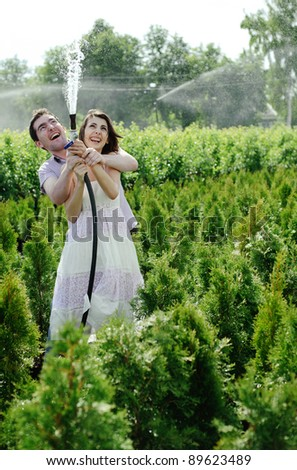 An image of a young couple playing in the garden - stock photo