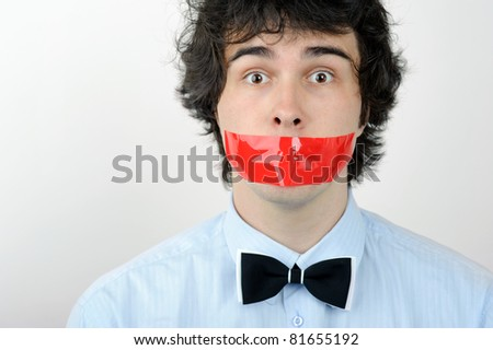 An image of a young man with adhesive on his mouth - stock photo
