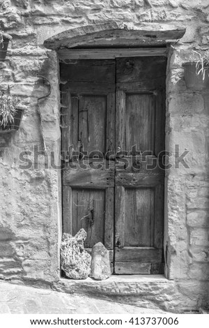An image of an old door in Italy. Black and white photography. - stock photo