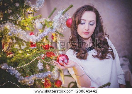 An image of beautiful young woman stands against christmas tree - stock photo