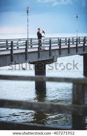 an image of bride and groom on a bridge at their wedding day