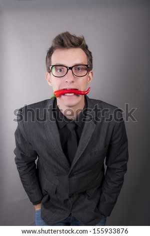an image of businessman with chili pepper in the mouth