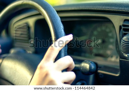 An image of female hand on steering wheel - stock photo