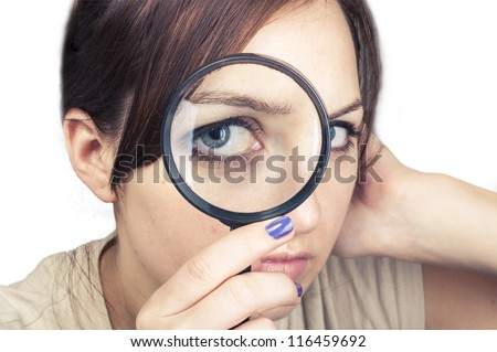 an image of girl with magnifying glass over her face - stock photo