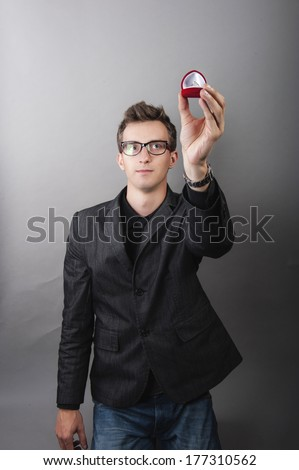 an image of man holding gold engagaement ring in red jewelery box - stock photo