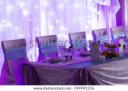 an image of tables setting at a luxury wedding hall - purple lights