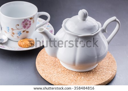 an image of teapot and tea cup over dark background