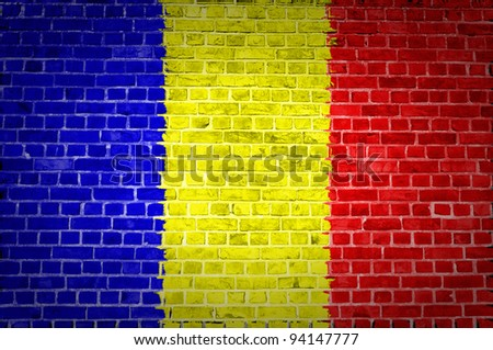 An image of the Chad flag painted on a brick wall in an urban location