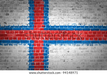 An image of the Faroe Islands flag painted on a brick wall in an urban location