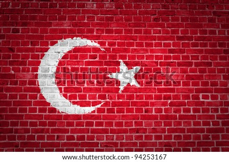 An image of the Turkey flag painted on a brick wall in an urban location