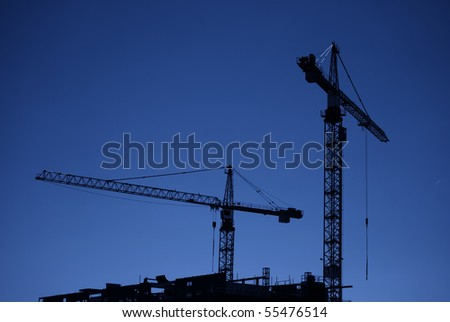 An image of two construction cranes silhouetted against a dark evening sky on a city centre building site. - stock photo