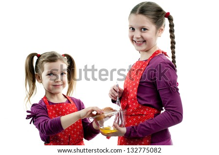 An image of two sisters cooking something