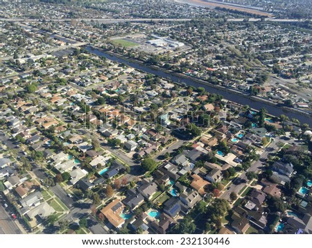 An image shot from an airplane shows what a neighborhood of homes looks like from an elevated perspective. - stock photo