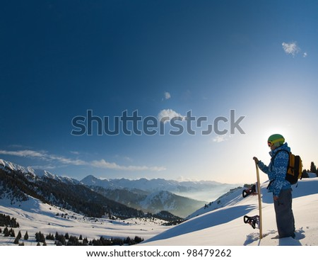 An image with a portrait of a female snowboarder wearing a helmet with a bright reflection in the glasses on the background of high snow-capped Alps in Grindelwald, Swiss - stock photo