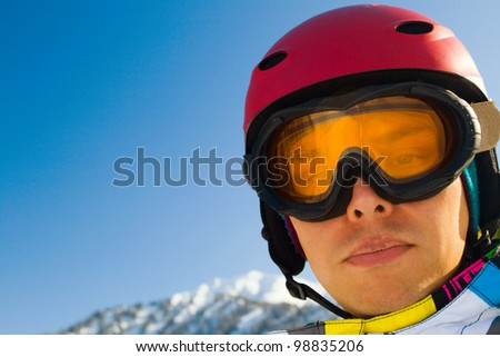 An image with a portrait of a snowboarder wearing a helmet and glasses on the background of high snow-capped Alps in Grindelwald, Swiss