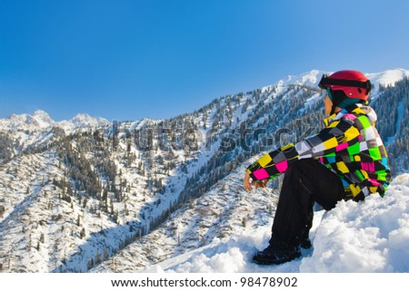 An image with sitting snowboarder with a helmet and glasses on the background of high snow-capped Alps in Austria