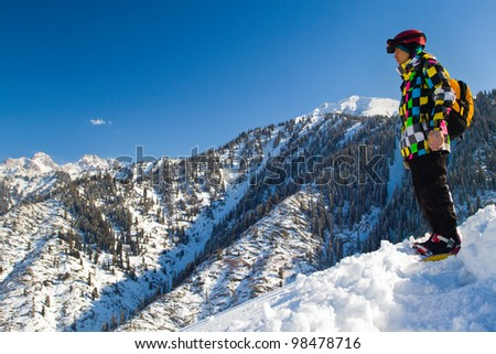 An image with standing snowboarder with a helmet and glasses on the background of high snow-capped Alps in Grindelwald, Swiss.