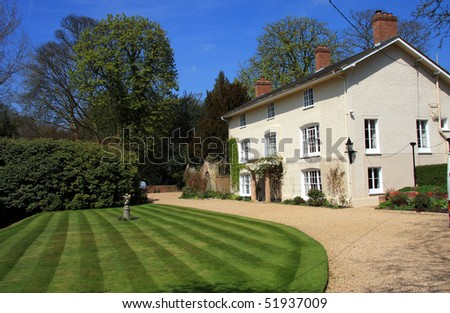 An impressive white family home with freshly mown lawn - stock photo
