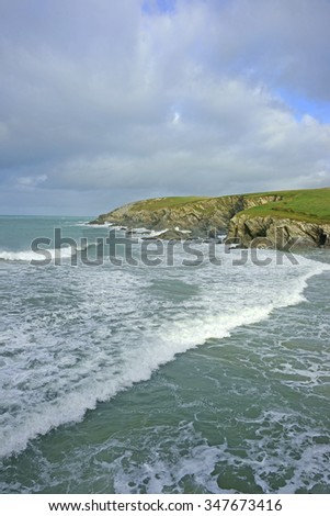 An incoming tide at Porth Joke beach near Newquay and on the South West Coastal Path under a stormy winter sky, North Cornwall, England, United Kingdom