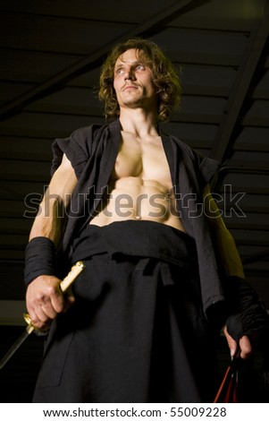 an incredibly muscular martial artist with samurai sword - stock photo