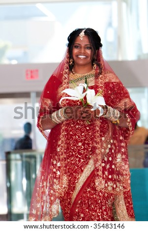 An indian bride in a red sari walks down the aisle - stock photo