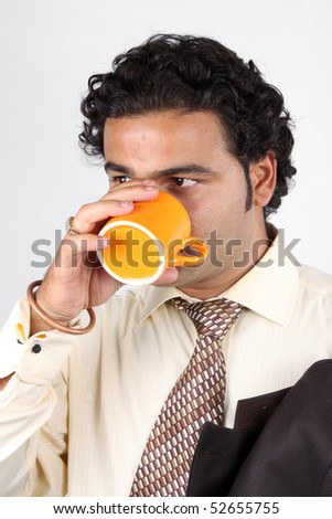 An Indian businessman drinking coffee from an orange mug, during an office break. - stock photo