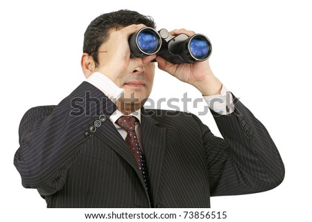 An Indian businessman in his late thirties looking through binoculars. - stock photo