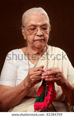 An Indian grandmother crocheting - stock photo