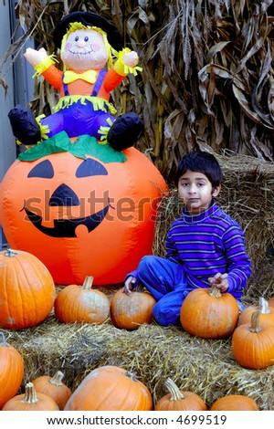 An indian kid having fun with the haloween pumpkins - stock photo