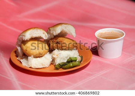 An Indian snack called Vada Pav which is like a potato burger or tikki n a bread, with a cup of tea