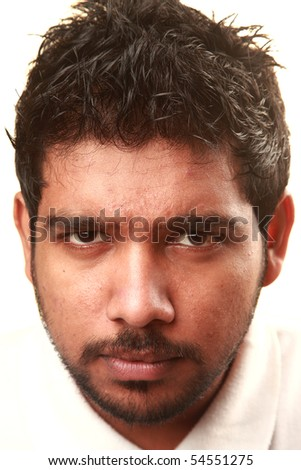 An Indian young man giving a sharp look - stock photo