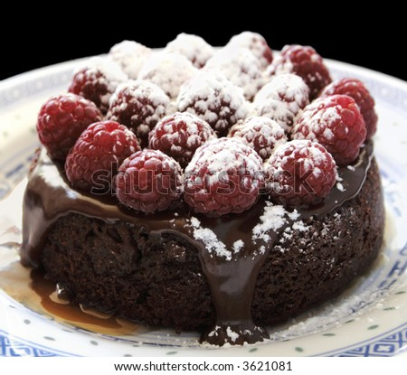 an individual-sized chocolate cake topped with ganache, fresh raspberries, powdered sugar and caramel sauce - stock photo