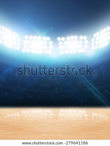 An indoor gynasium with an unmarked wooden floor under illuminated floodlights - stock photo