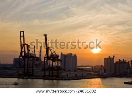 An industrial area on the coast under dusk skies - stock photo