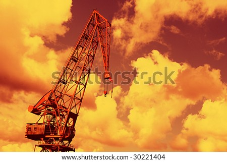 An industrial crane over a red dramatic sky
