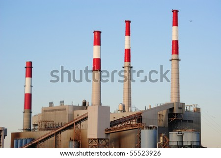 An industrial factory with smoke stacks. - stock photo