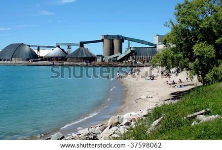 an industrial salt mine on a lake - stock photo