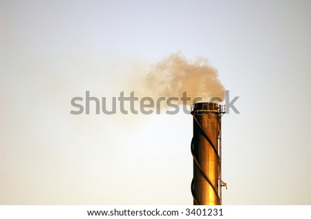 An industrial smokestack emitting polutants into the atmosphere. - stock photo