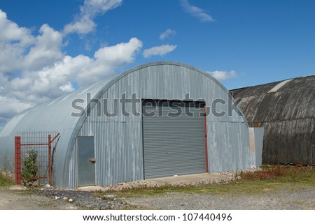 An industrial unit made from corrugated metal sheets with a roller shutter and door on rough ground.