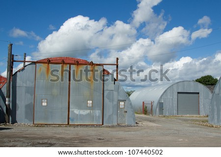 An industrial unit made from corrugated metal sheets with a sliding shutter and door on rough ground.