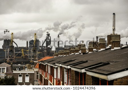An industrial urban view. There are houses' roofs with chimneys on the foreground and a steelworks with smoking pipes and a gray smoky sky on the background. The photo was shot in IJmuiden, Holland.