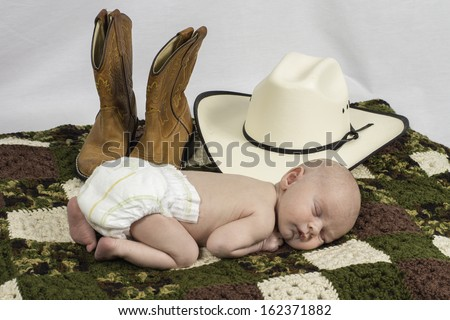 An infant baby laying down surrounded by a cowboy hat and boots. - stock photo