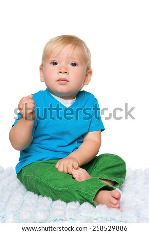 An infant boy is sitting on the white carpet