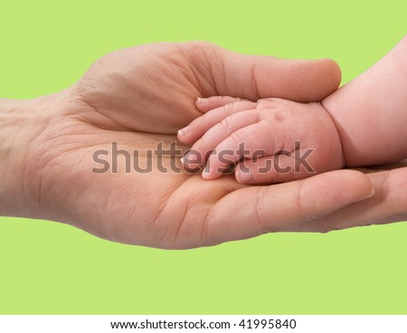 An Infant Hand In An Adult Hand Against A Green Background - stock photo